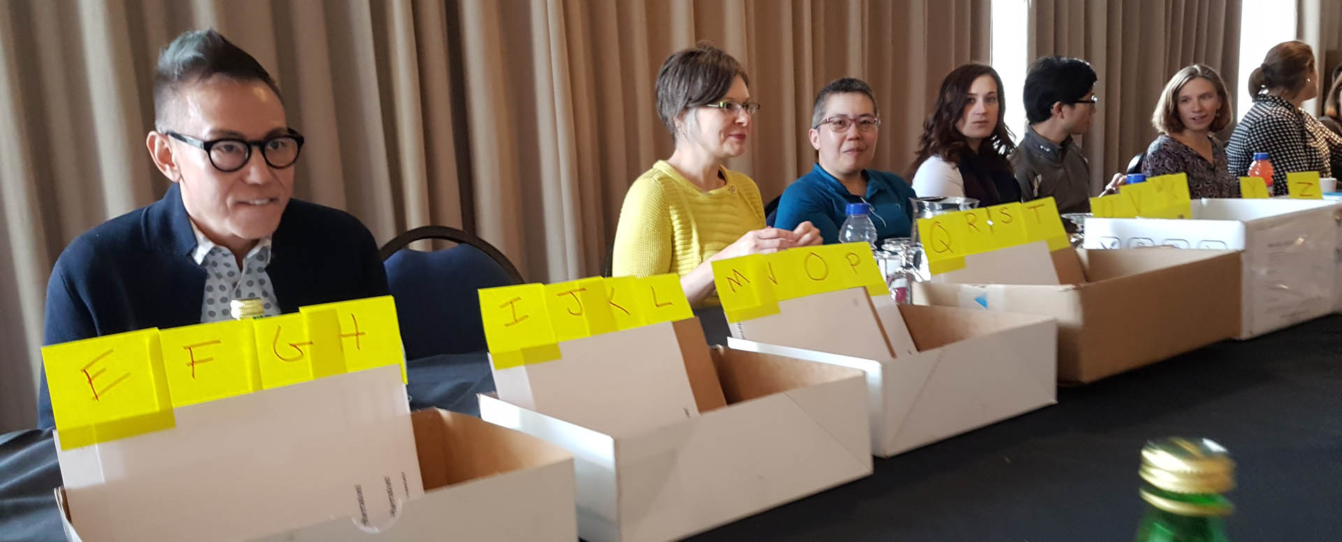 A group of volunteers sits at a table and sorts packets at the 2018 conference in Vancouver.