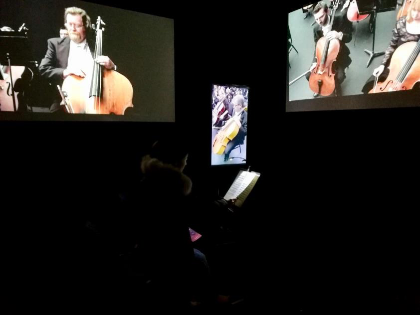 A man sits in a room with a virtual orchestra.
