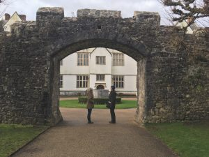 Two people standing under a stone archway.