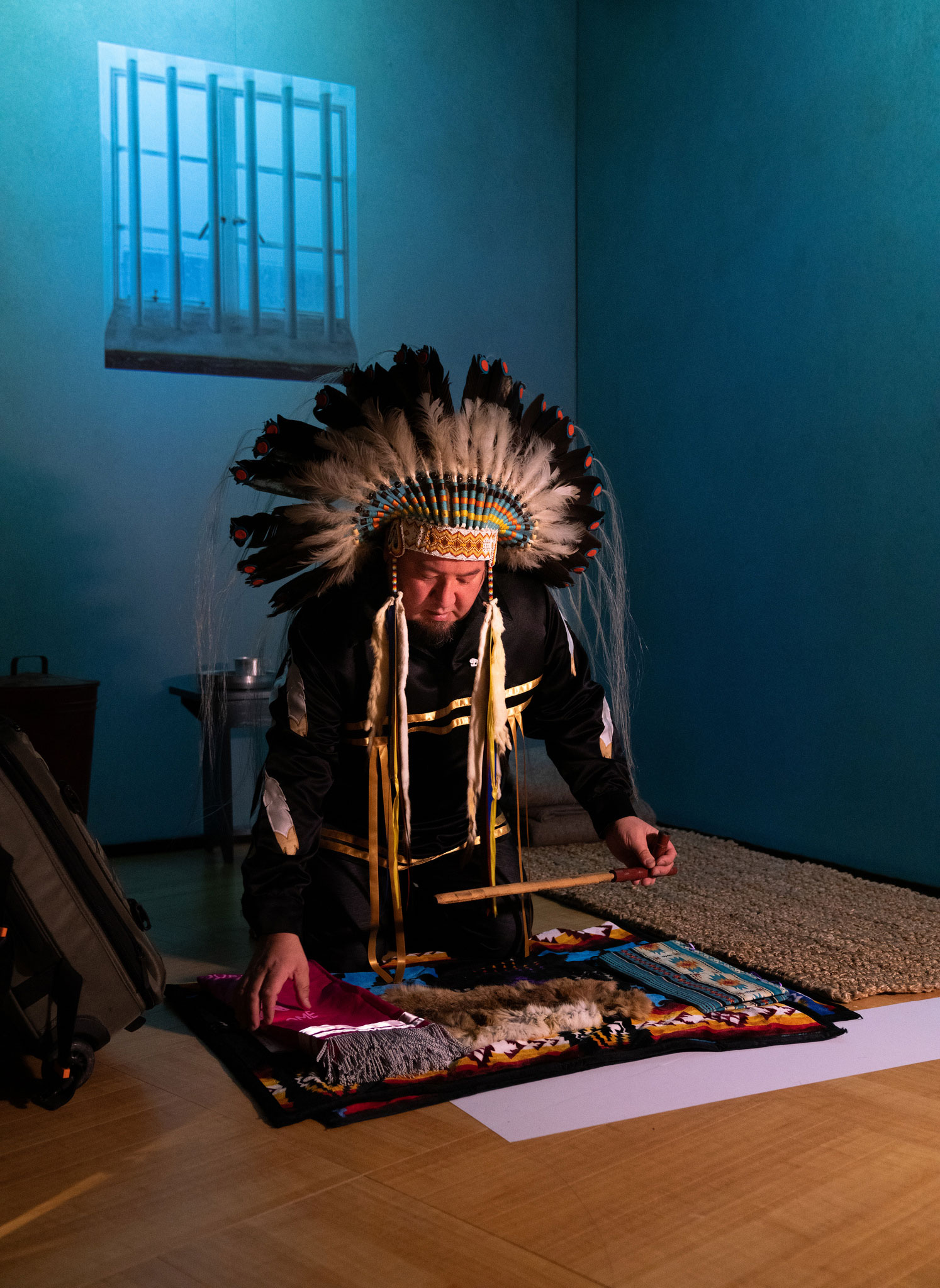 An male figure wearing a feather head-dress spreads a blanket with sacred objects and medicine.