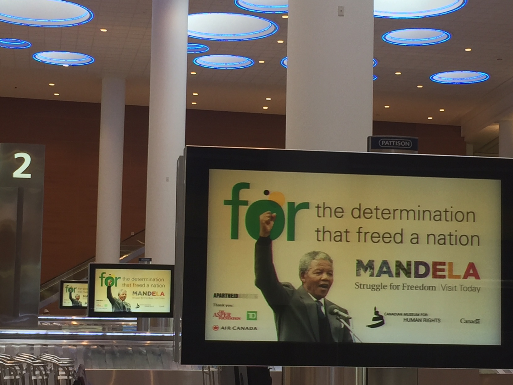 Baggage carousels featuring multiple screens with Mandela raising his fist.