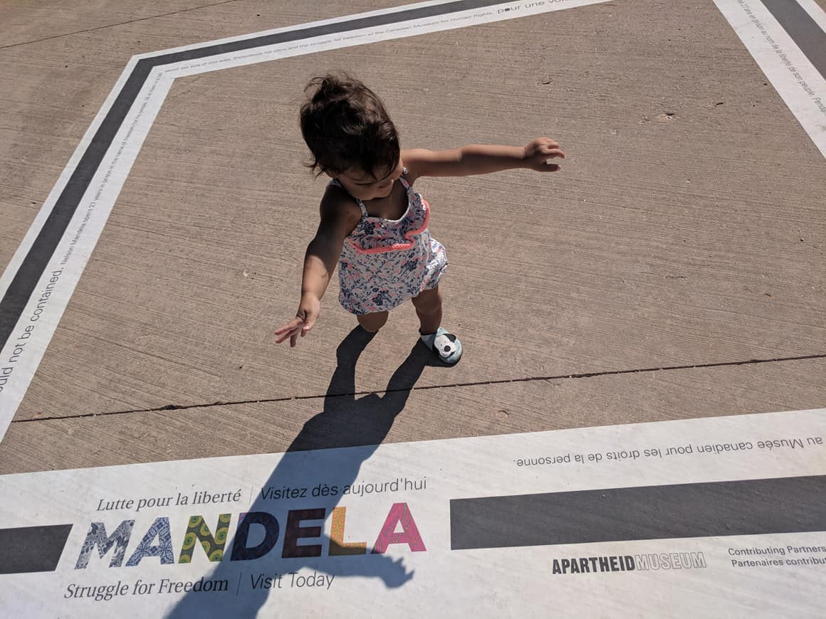 Small child walking on a concrete sidewalk with a large decal on it.
