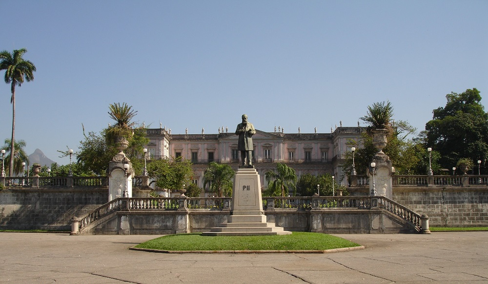Main facade of the National Museum with Rio de Janeiro landscape in the background and statue of Emperor Dom Pedro II standing in front.